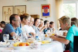 Like minded families eating breakfast together on an adventure holiday in Europe