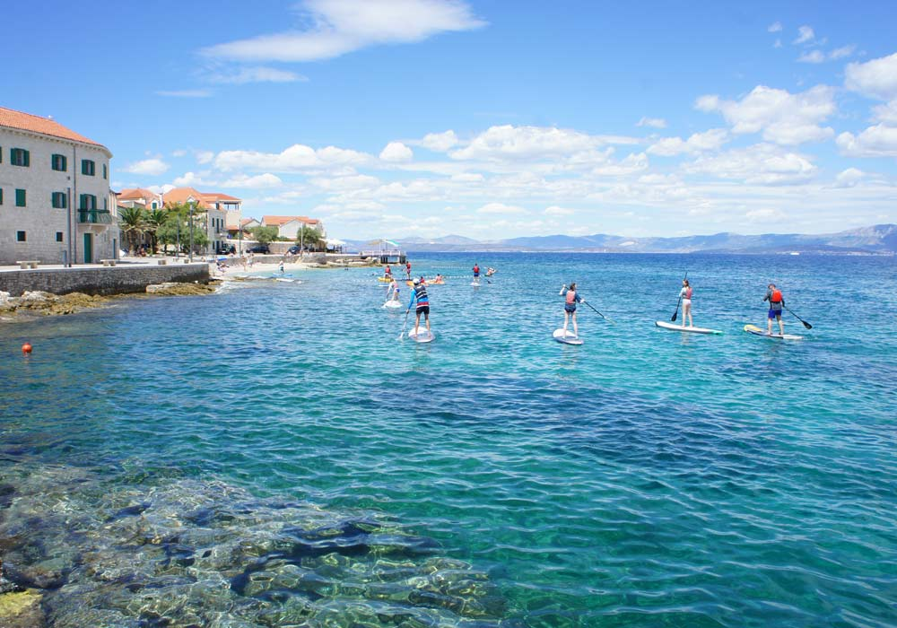 Standup paddle board tours on Brac island, perfect for families being active.
